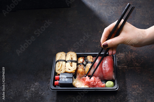 Fototapeta Sushi lunch. Pudełko z sushi .Jedzenie sushi pałeczkami prosto z tacki. obraz