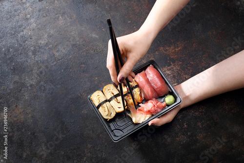 Fototapeta Sushi. Jedzenie na wynos. Jedzenie sushi pałeczkami prosto z tacki. obraz