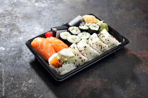 Fototapeta Sushi lunch. Hosomaki, futomaki i nigiri zestaw sushi. Tacka z kawałkami sushi , imbirem , wasabi i sosem sojowym na ciemnym tle. obraz