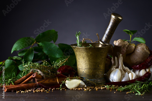 Different herbs and spices with ginger on a wooden table.