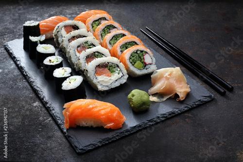 Fototapeta Sushi. . Apetyczne, różnorodne sushi na kamiennym talerzu. Kompozycja na ciemnym tle. obraz
