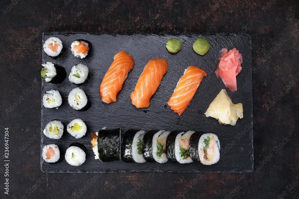 Obraz Sushi menu. Apetyczne, różnorodne sushi na kamiennym talerzu. Kompozycja na ciemnym tle. fototapeta, plakat