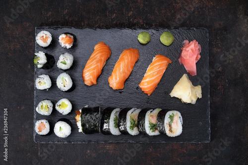 Fototapeta Sushi menu. Apetyczne, różnorodne sushi na kamiennym talerzu. Kompozycja na ciemnym tle. obraz