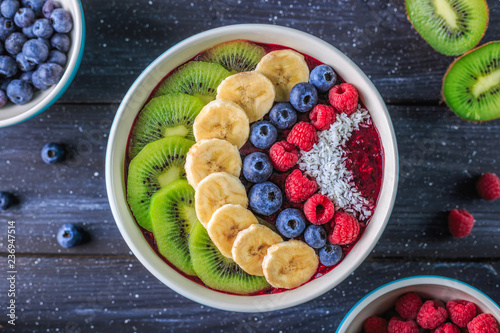 Healthy breakfast with delicious acai smoothie in bowl on dark background Canvas Print