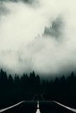 road in dark landscape with mountain shrouded in fog - 236948906