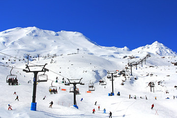 Many tourists using the cablecar for skiing , snowboarding on the beautiful winter snow Mountain Ruapehu in the Northern island of New Zealand on a bright sunny day.