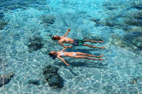 Happy couple swimming in the transparent turquoise sea
