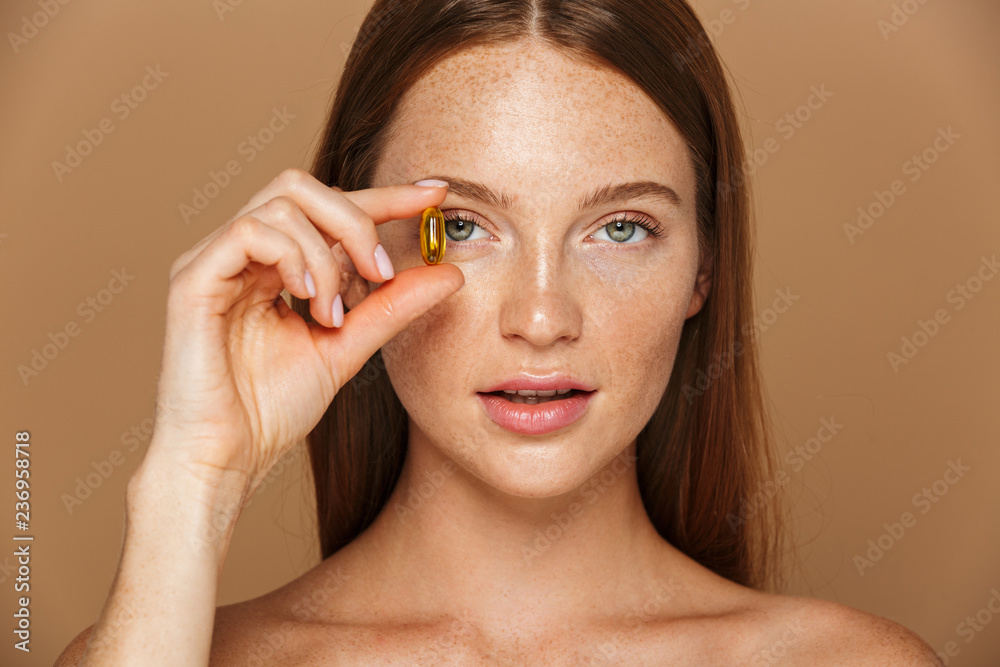 Fototapeta Beauty image of caucasian shirtless woman 20s holding vitamin pill, isolated over beige background