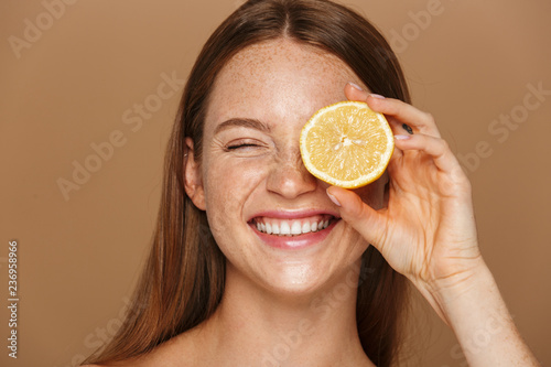 Fotografía Beauty image of smiling shirtless woman with long hair holding piece of orange,