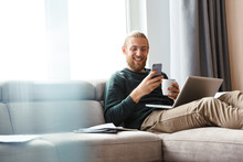 Young Bearded Man Sitting In Home Using Laptop Computer And Mobile Phone.