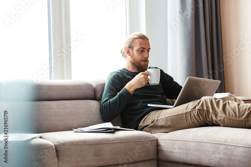 Concentrated young bearded man sitting in home using laptop computer.