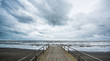 Rusty bridge stretching into the lifeless sea, Caspian sea under blue sky in early September, snag on the beach