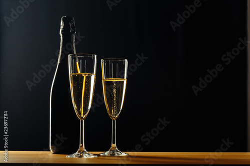 Vászonkép bottle of champagne and glasses over dark background
