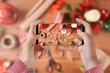 Girl in a cozy knitted sweater taking photo with phone of Christmas decorations and handmade gifts on wooden desk