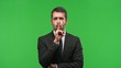 businessman showing a sign of silence putting finger in mouth on green screen chroma key background