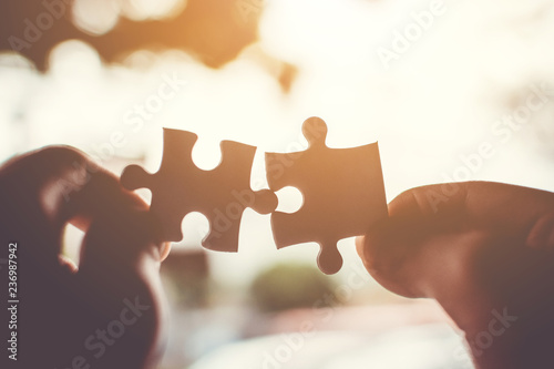 Two hand connecting jigsaw puzzle. Concept of partnership and teamwork in business strategy