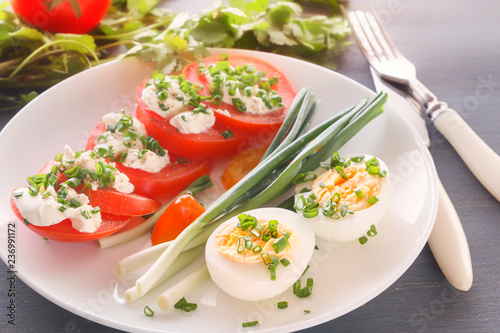 Half boiled eggs with tomatoes, green onions sprinkled with greens in a white plate on a gray wooden table. Close-up