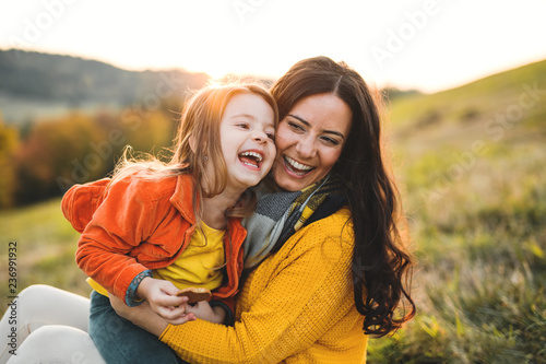 Fototapeta A portrait of young mother with a small daughter in autumn nature at sunset. obraz