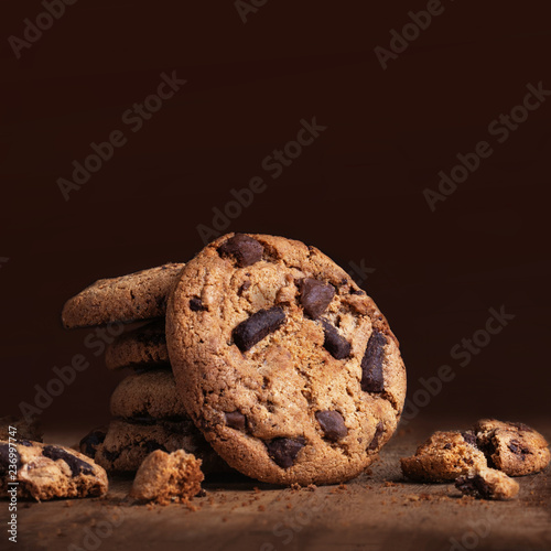 Chocolate cookies on wooden table. Chocolate chip cookies shot on coffee toned background with copy space for text, closeup.