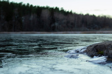 Frozen Lake With Rock In The Foreground And Blurry Trees In The Distance From Shallow Depth Of Field. Horizontal.