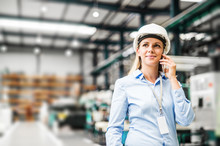 A Portrait Of An Industrial Woman Engineer Standing In A Factory, Making A Phone Call.