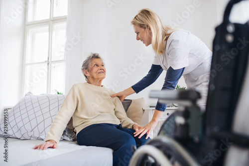 Obraz A health visitor talking to a senior woman sitting on bed at home. - fototapety do salonu