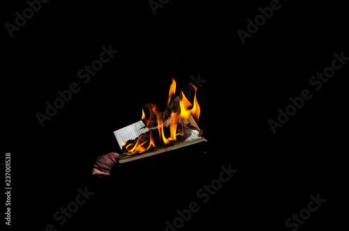 Fotografiet  Burning book on a black background