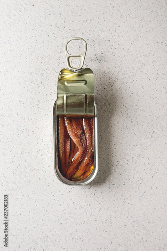 Pickled salted anchovies fillet in oil in open tin can over grey spotted background Wallpaper Mural