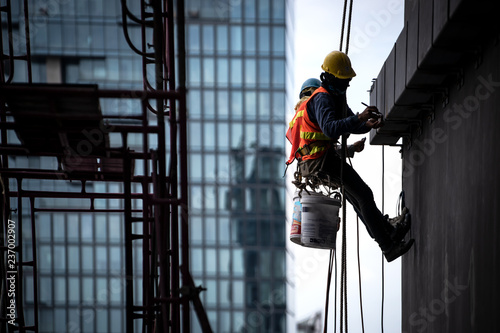 Obraz Construction worker wearing safety harness and safety line working at high place - fototapety do salonu