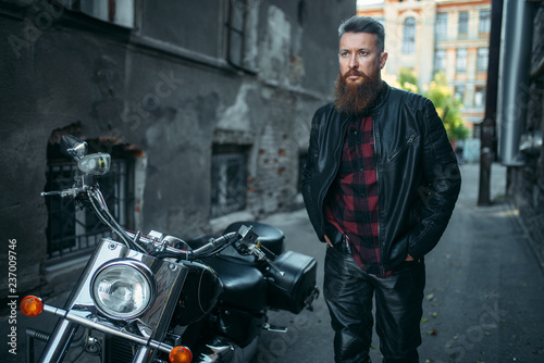 Foto Bearded biker in leather clothes against chopper