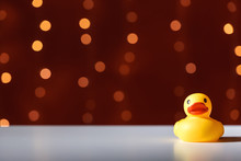 Rubber Duck Toy On A Shiny Light Dark Red Background