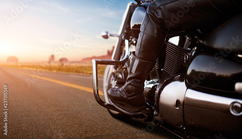 Biker riding on chopper, view from rear wheel