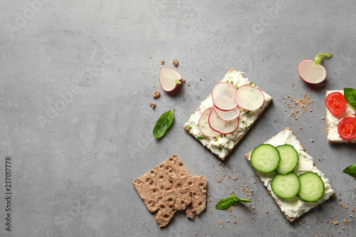 Tasty snacks with cream cheese and vegetables on gray table, flat lay. Space for text