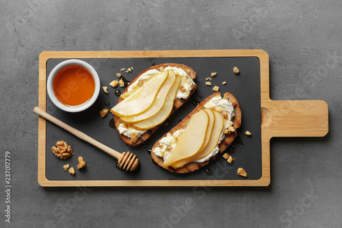 Toasted bread with tasty cream cheese and pear on gray table, flat lay