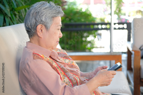 Fotografia  asian elder woman holding mobile phone at home