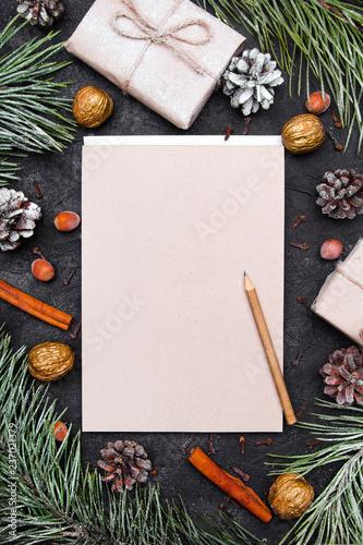 Fototapeta  Tło na Boże Narodzenie  z pustą kartka papieru otoczoną świątecznymi dekoracjami