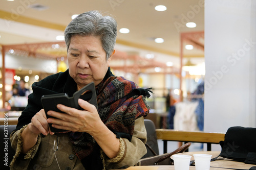 Photographie  asian elder woman holding mobile phone at restaurant