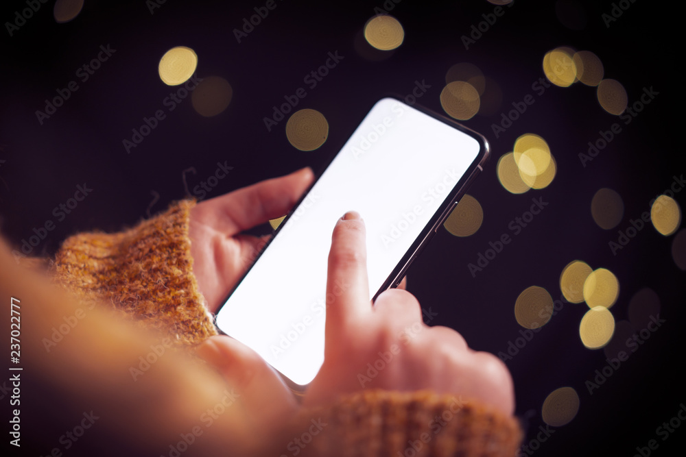 Fototapeta Woman using mobile smart phone at night with dramatic lighting, city lights and shallow depth of field. Blank screen with bright lighting for design mockups.