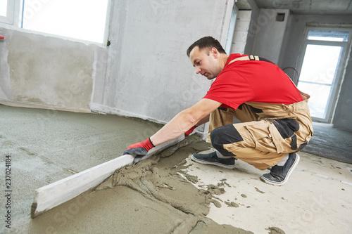 Obraz Floor cement work. Plasterer smoothing floor surface with screeder - fototapety do salonu