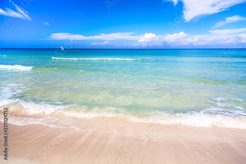The tropical wonderful beach of Varadero in Cuba with sailboat on a sunny day with turquoise water and blue sky. Vacation background.