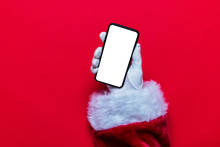 Santa Claus Christmas Hand Holding A Phone Against A Red Background