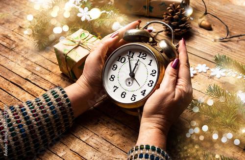 Fotografie, Obraz  Woman holding a vintage clock in festive environment