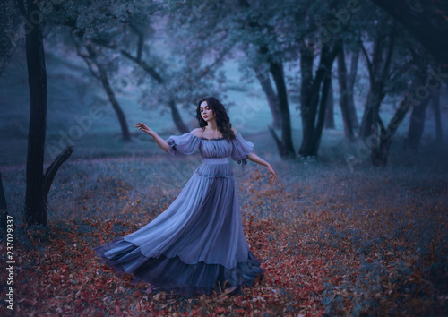 a mysterious girl with wavy dark hair is dancing alone on fallen autumn leaves i Wallpaper Mural