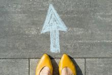 Female Feet With Arrow Painted On The Grey Sidewalk