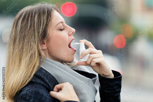 Fotomural Illness young woman applying a analgesic spray to soften the throat in the street