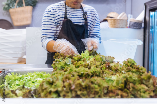 Fresh Salad bar counter with person's hands lifting Lettuce into a plate for healthy and diet meal with smooth light and shadow.