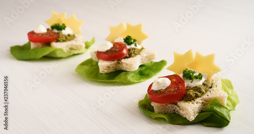 creative party canapes on lettuce with tomato, pesto and cheese in star shape for christmas or new year, light background with copy space