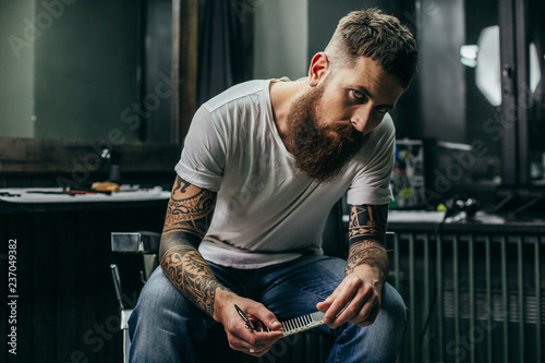 Canvas Print Calm bearded barber sitting and looking while holding comb