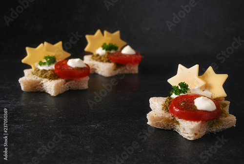 vegetarian canapes for christmas with tomato, pesto and cheese in star shape on a dark stone slab with copy space