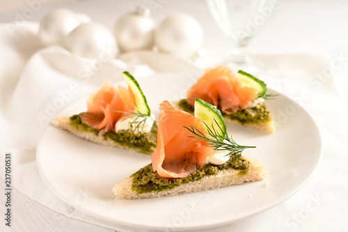 festive canapes with smoked salmon, pesto, cucumber and dill garnish, white table cloth and christmas decoration, copy space